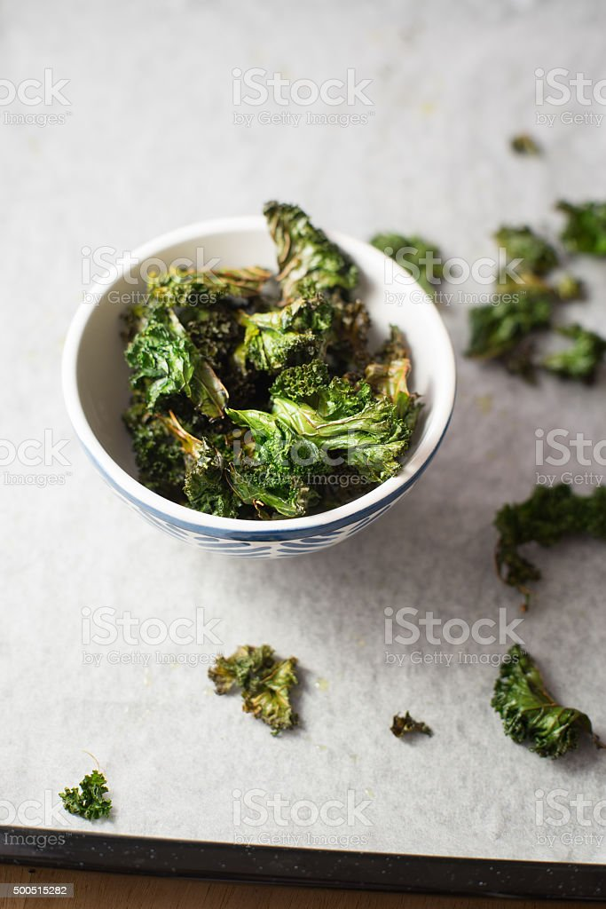 Homemade curly kale chips in small bowl. Selective focus stock photo