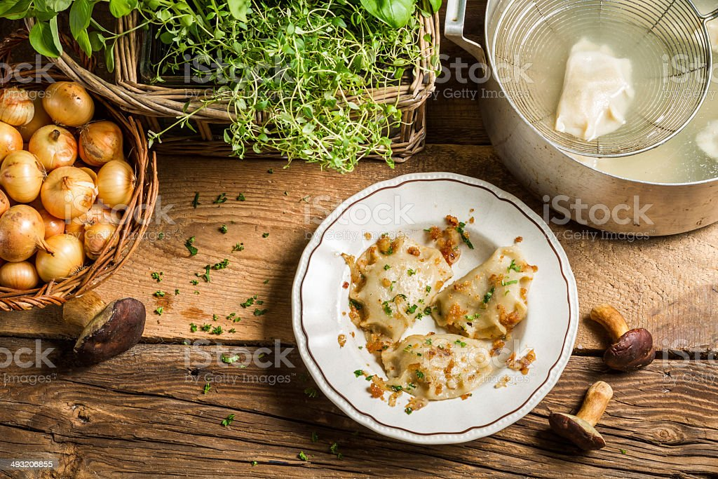 Homemade dumplings with mushrooms fried with onion and parsley stock photo