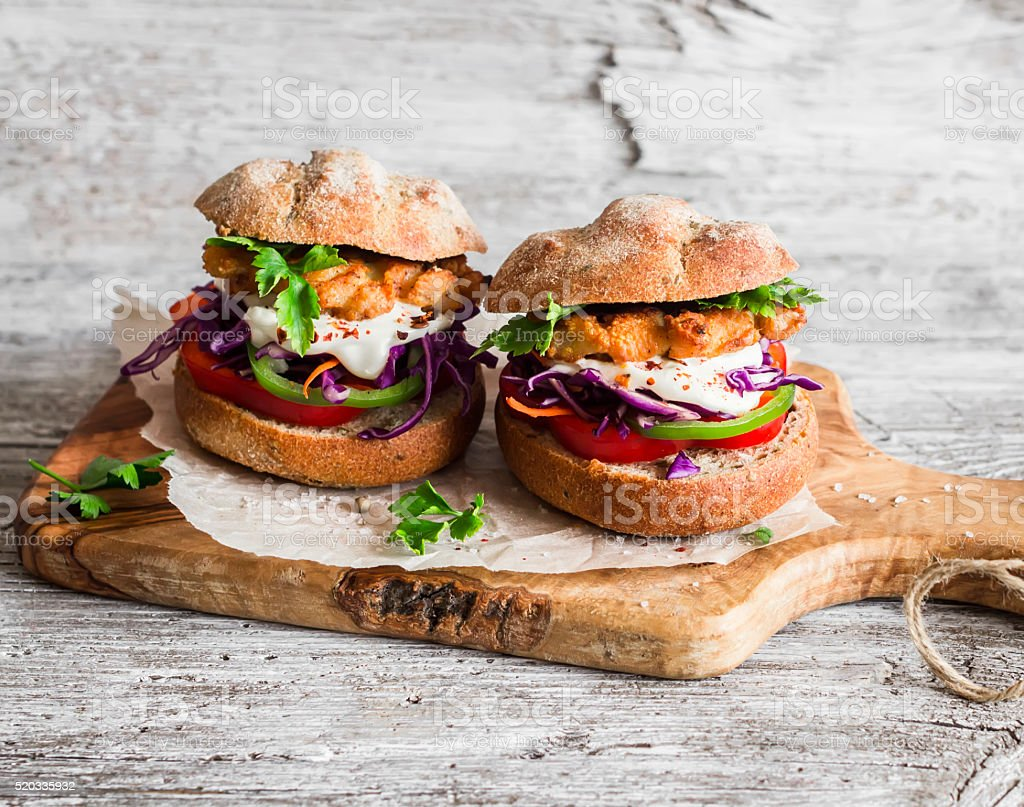 Homemade  fish burger on a light rustic wooden board stock photo