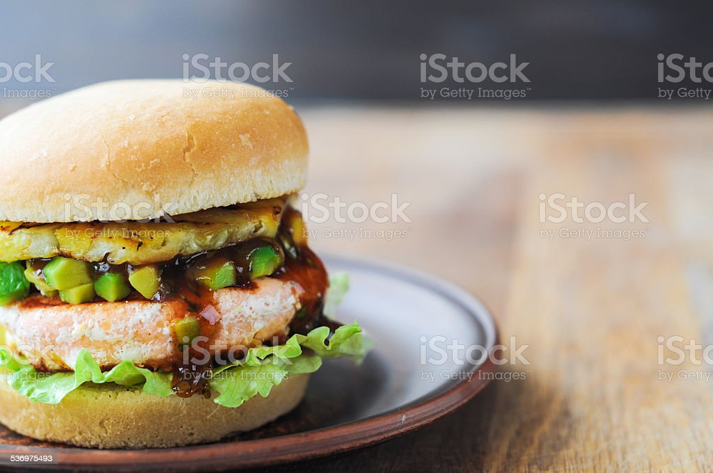 Homemade fish burger with salmon, avocado and pineapple.Close up stock photo