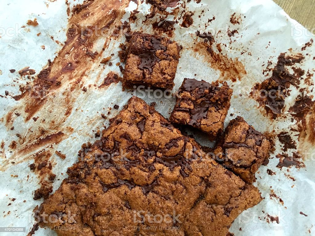 Homemade flourless nut butter blondies with chocolate on parchment paper stock photo
