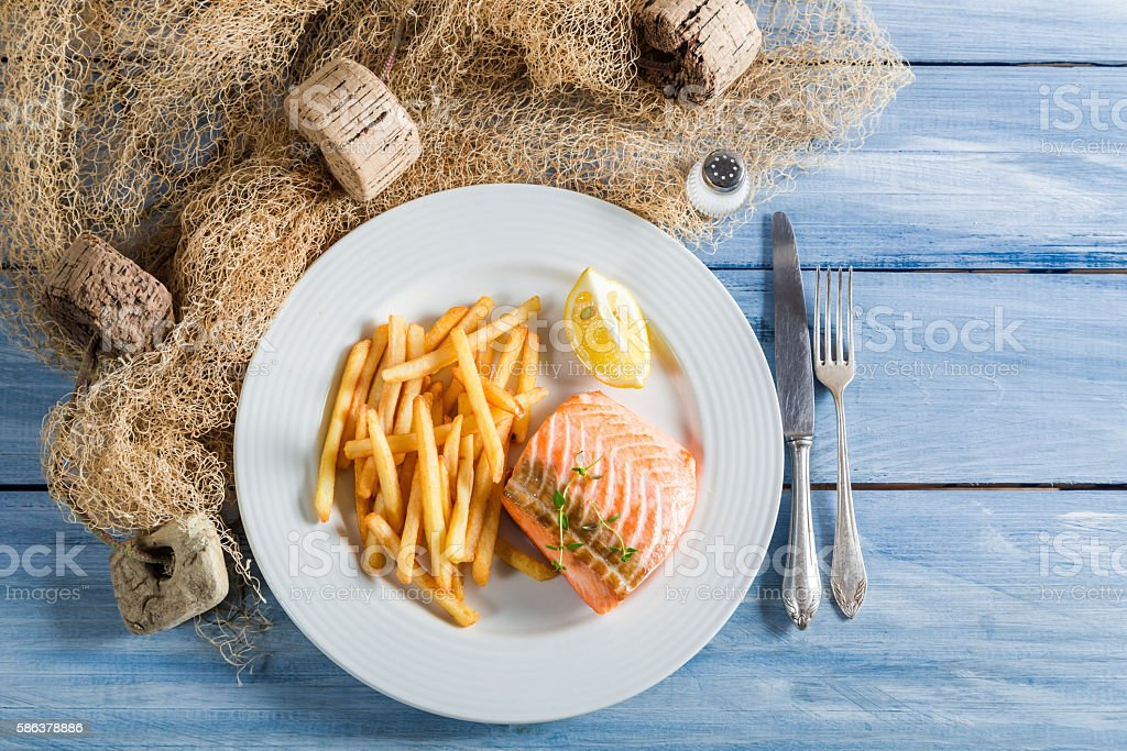 Homemade french fries with fresh salmon with lemon stock photo