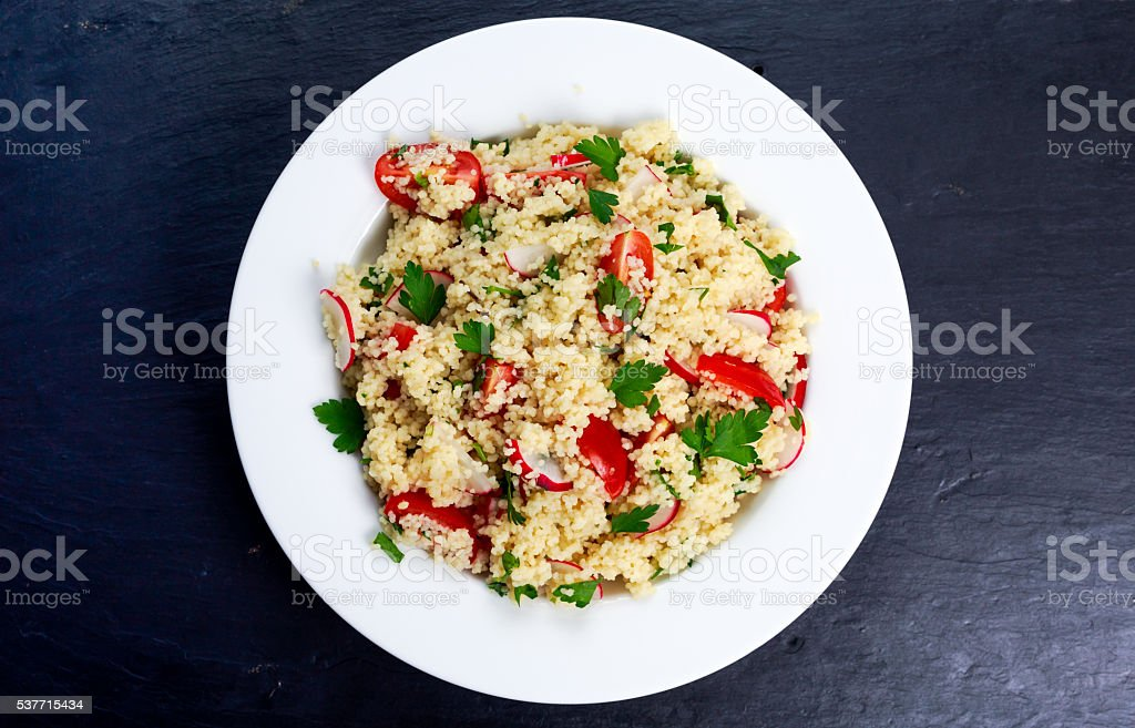 Homemade Fresh Couscous salad with vegetables, in white plate. stock photo