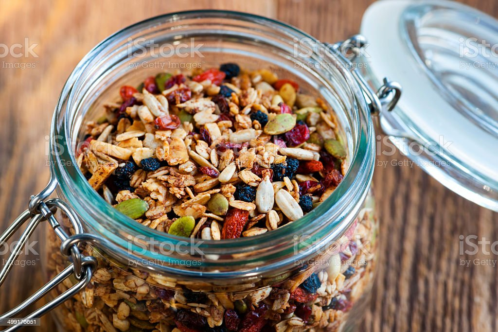 Homemade granola in open glass jar stock photo