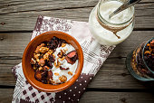 Homemade granola with organic yogurt in jar.