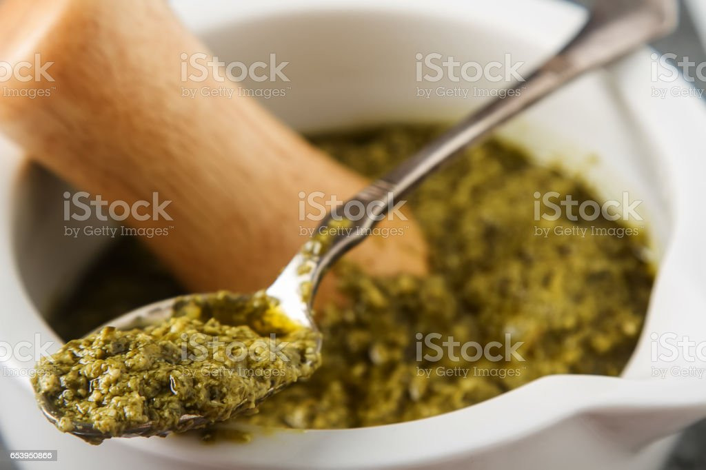 Homemade green pesto sauce with basil and pine nuts in white mor stock photo