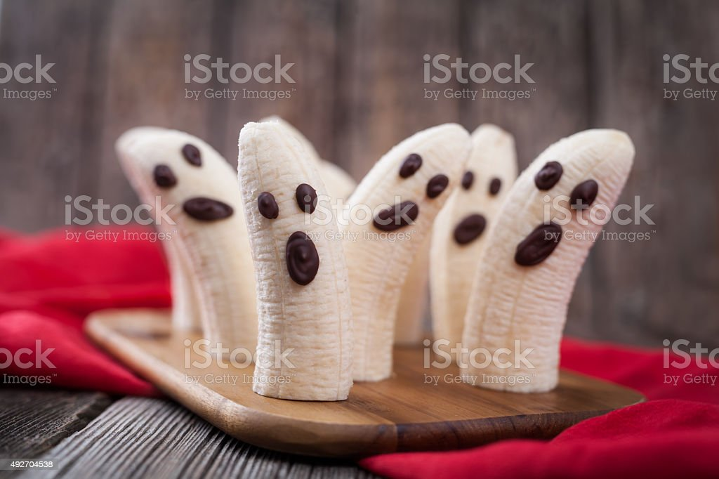 Homemade halloween scary banana ghosts monsters with chocolate faces. Healthy stock photo