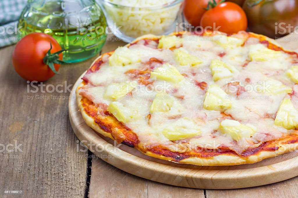 Homemade ham, bacon and pineapple Hawaii pizza stock photo