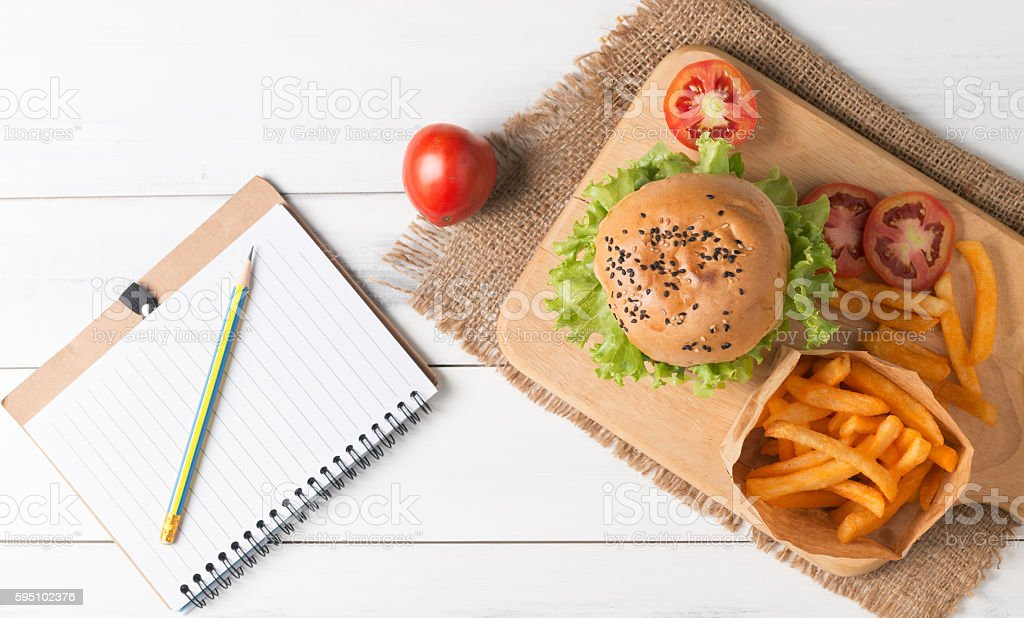 Homemade hamburger with french fries and notebook stock photo