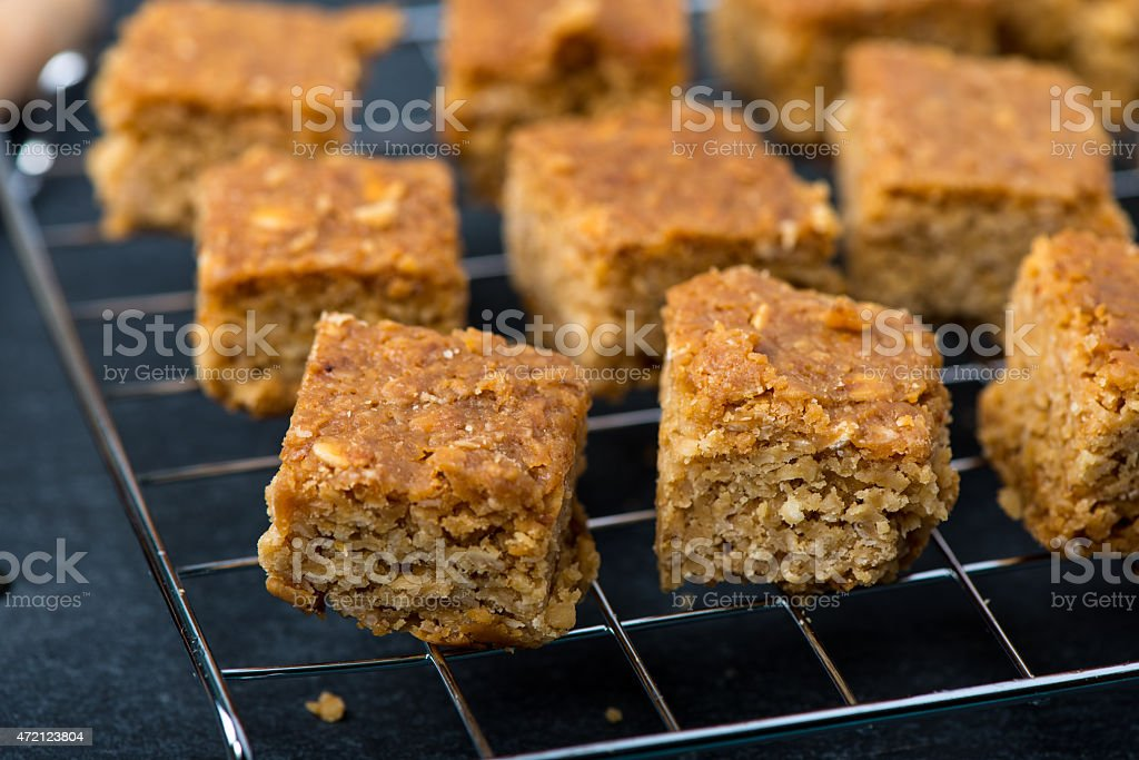 Homemade healthy flapjacks with honey on cooling rack stock photo