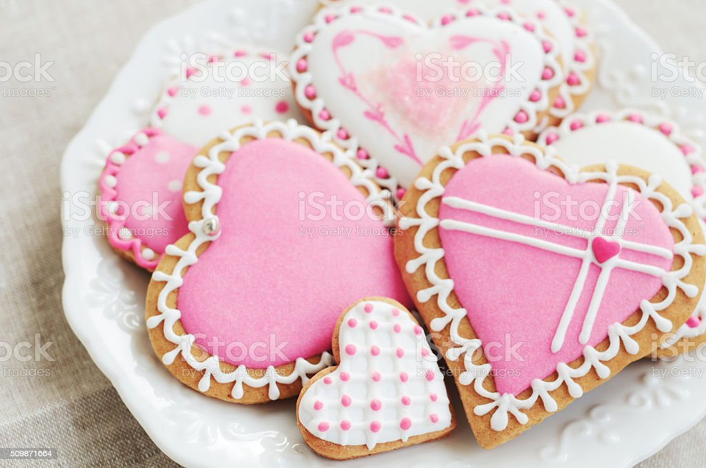 Homemade heart shaped sugar cookies with icing on white plate stock photo