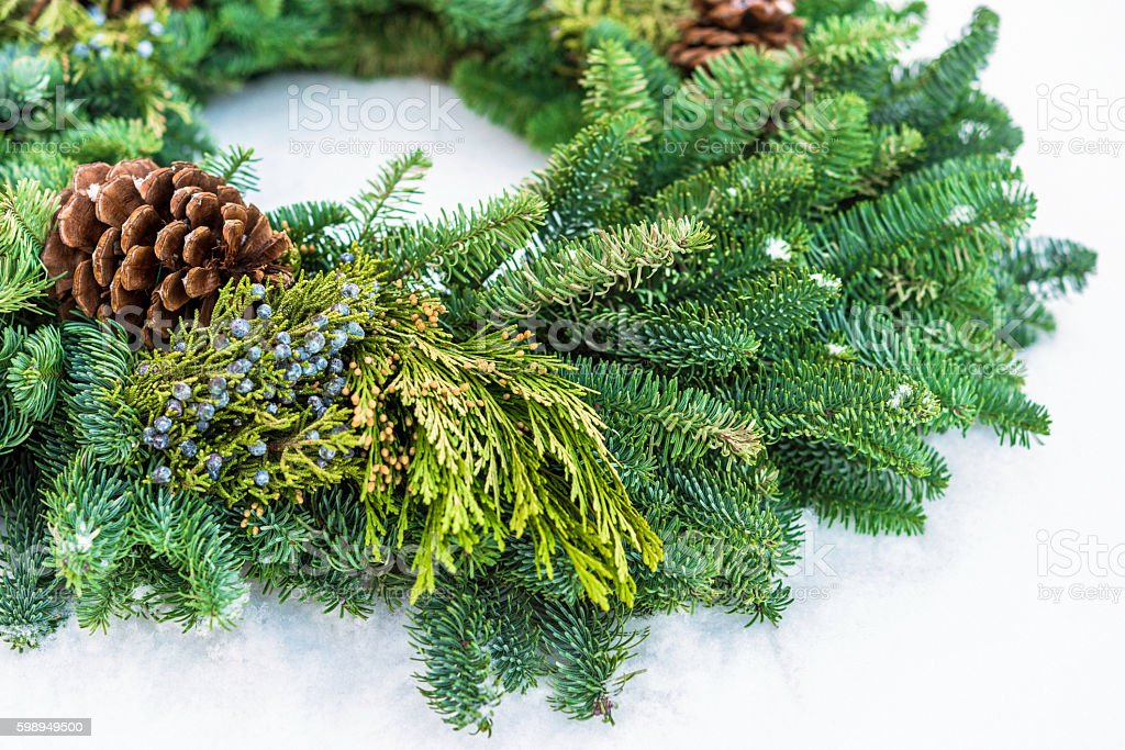 Homemade Holidays. Christmas wreath with real greenery in real snow stock photo