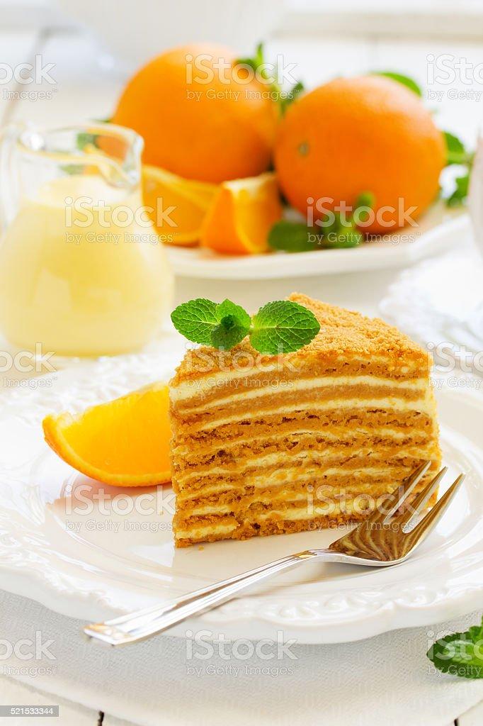 Homemade honey cake with orange cream on a white plate. stock photo