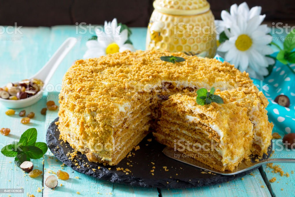 Homemade honey cake with sour cream on a wooden table with raisins and nuts. stock photo