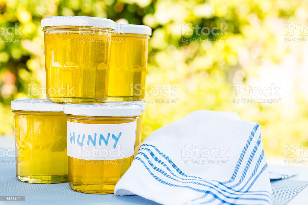 Home-made honey in jars outdoors stock photo