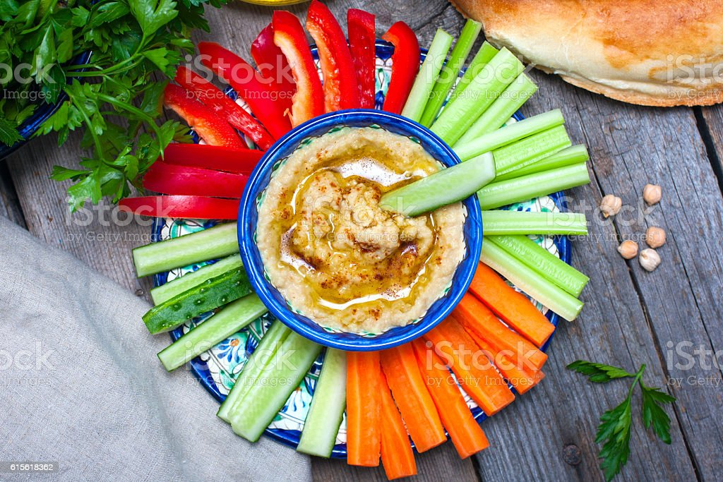 Homemade hummus with fresh vegetables, top view stock photo