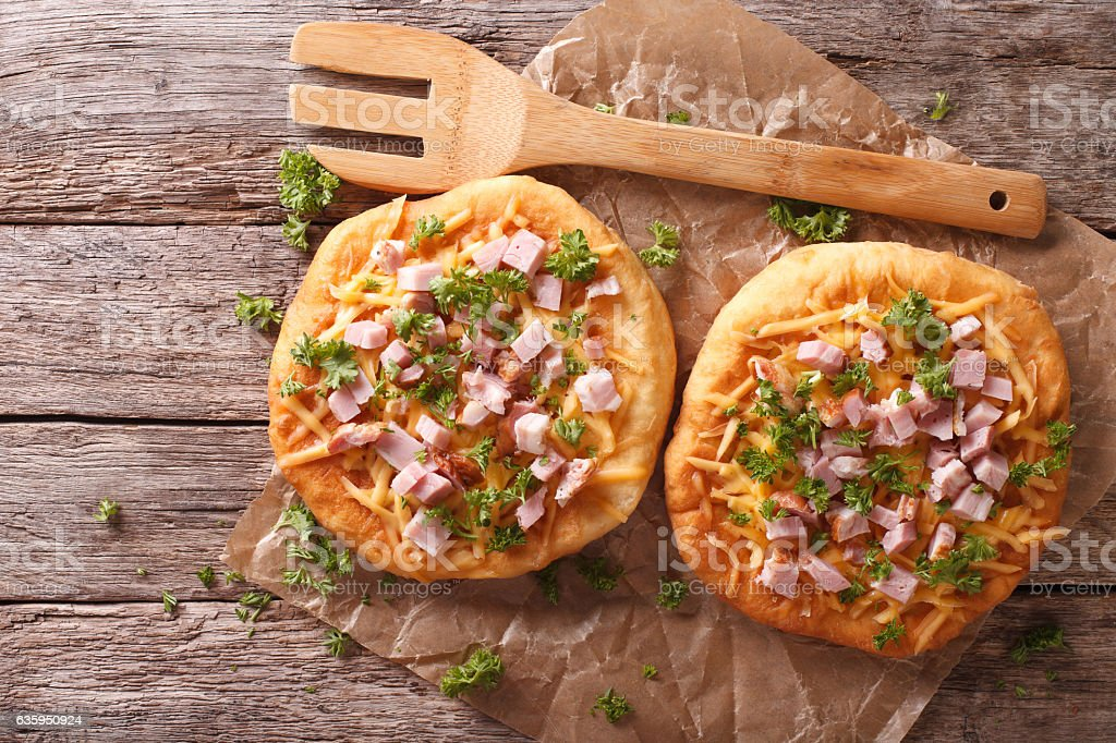 Homemade Hungarian langos with ham and cheese close-up. horizontal stock photo
