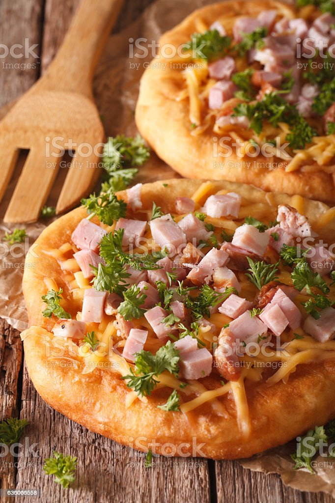 Homemade Hungarian langos with ham and cheese close-up. Vertical stock photo