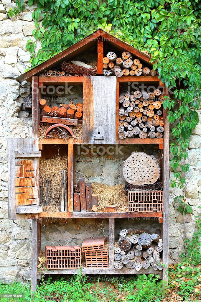 Homemade insects hotel house in garden with bricks and logs stock photo