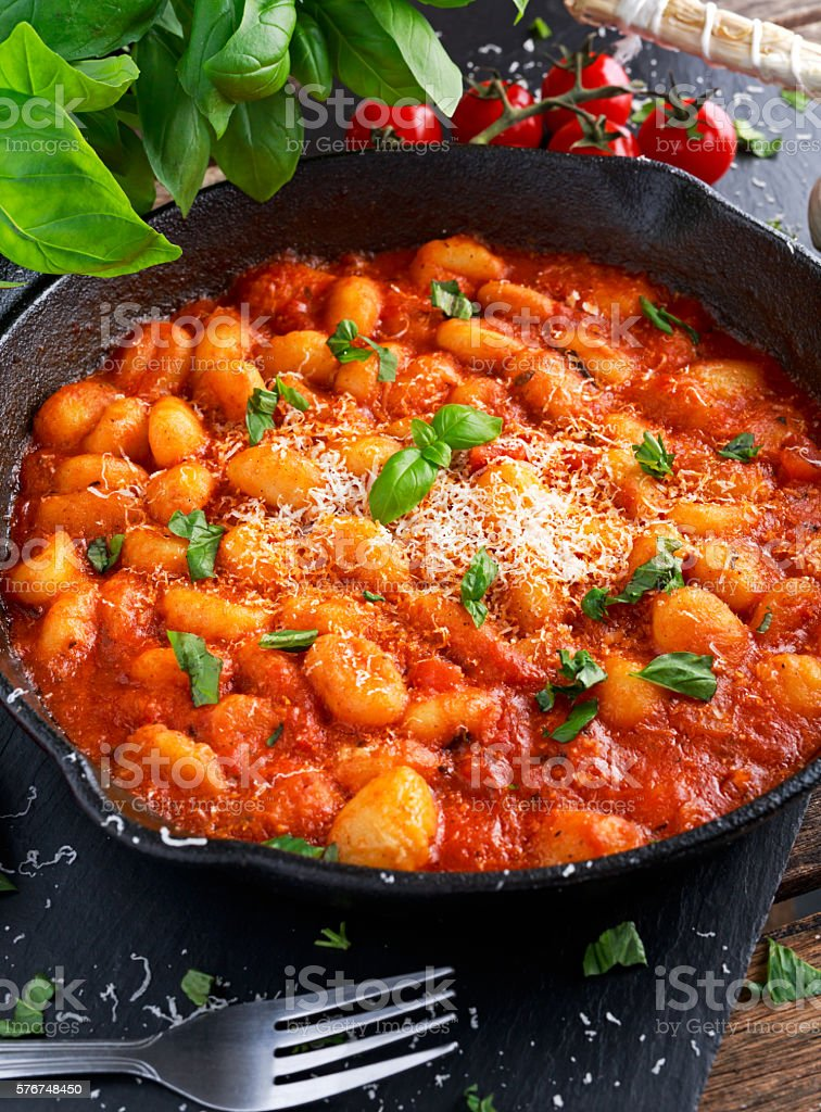 Homemade Italian Gnocchi with marinara sauce, cheese in iron pan stock photo