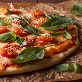 Homemade italian pizza with mozzarella, tomatoes and basil leaves.