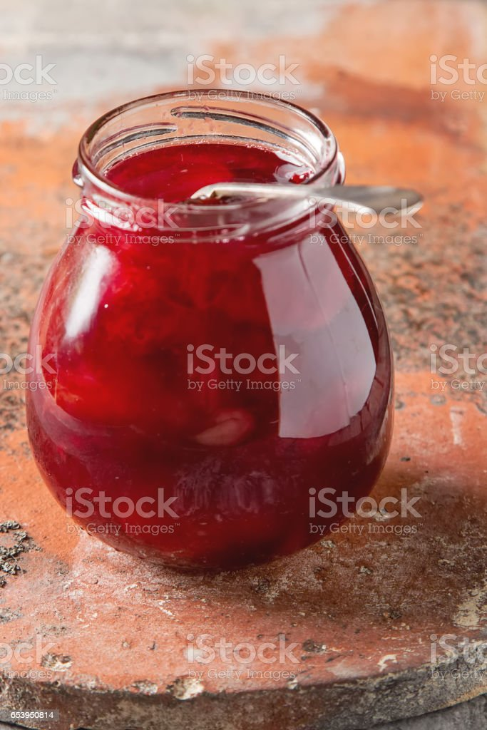 Homemade jam of plums with cinnamon and fresh fruits on wooden b stock photo