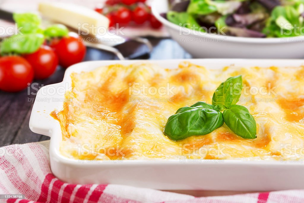 Homemade lasagna and green salad on a brightly lit table royalty-free stock photo