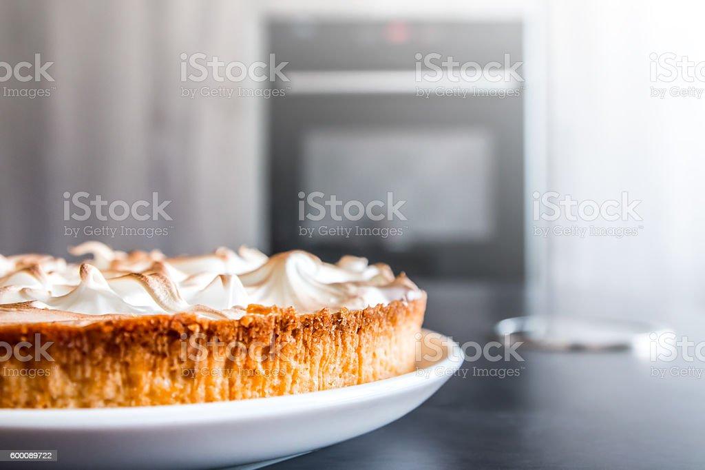 Homemade lemon meringue pie baked shot on gray kitchen island stock photo