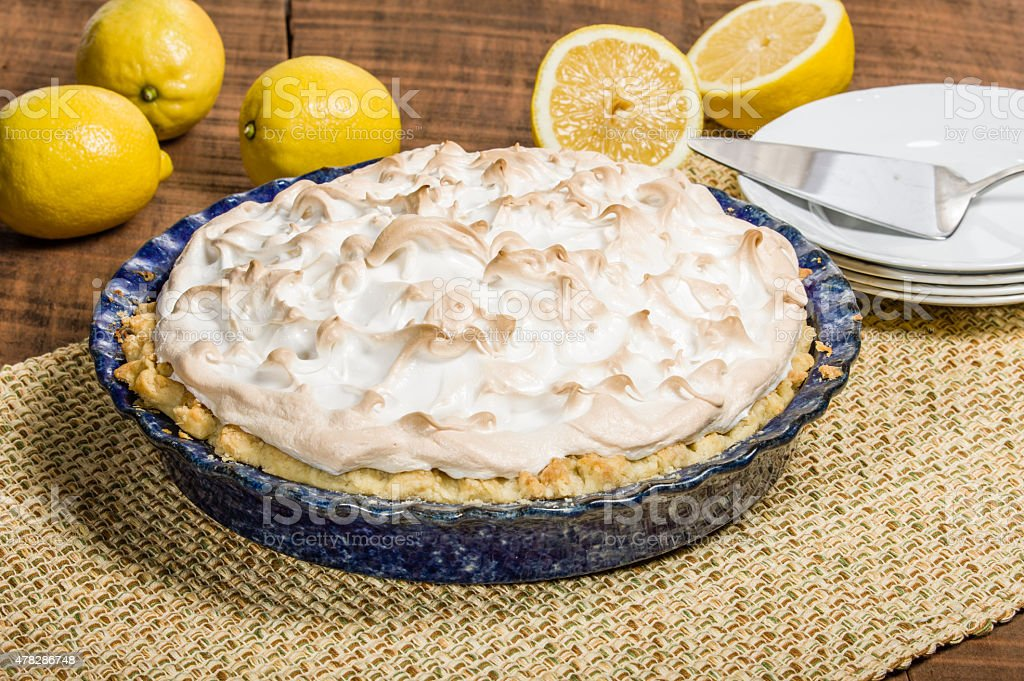 Homemade lemon meringue pie with lemons stock photo