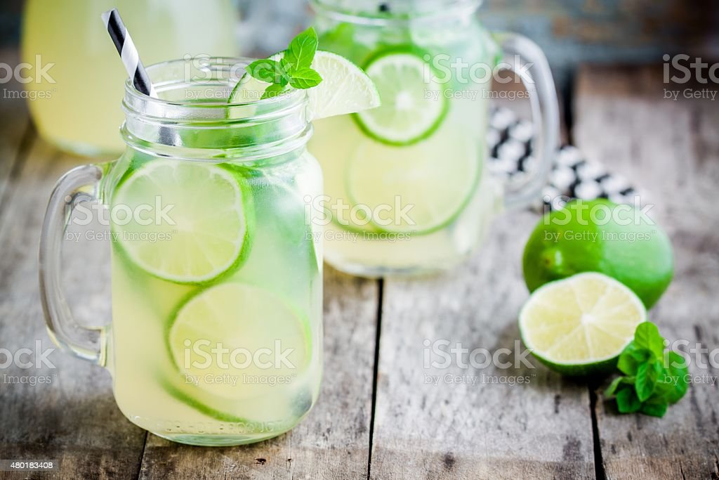 homemade lemonade with lime, mint in a mason jar stock photo