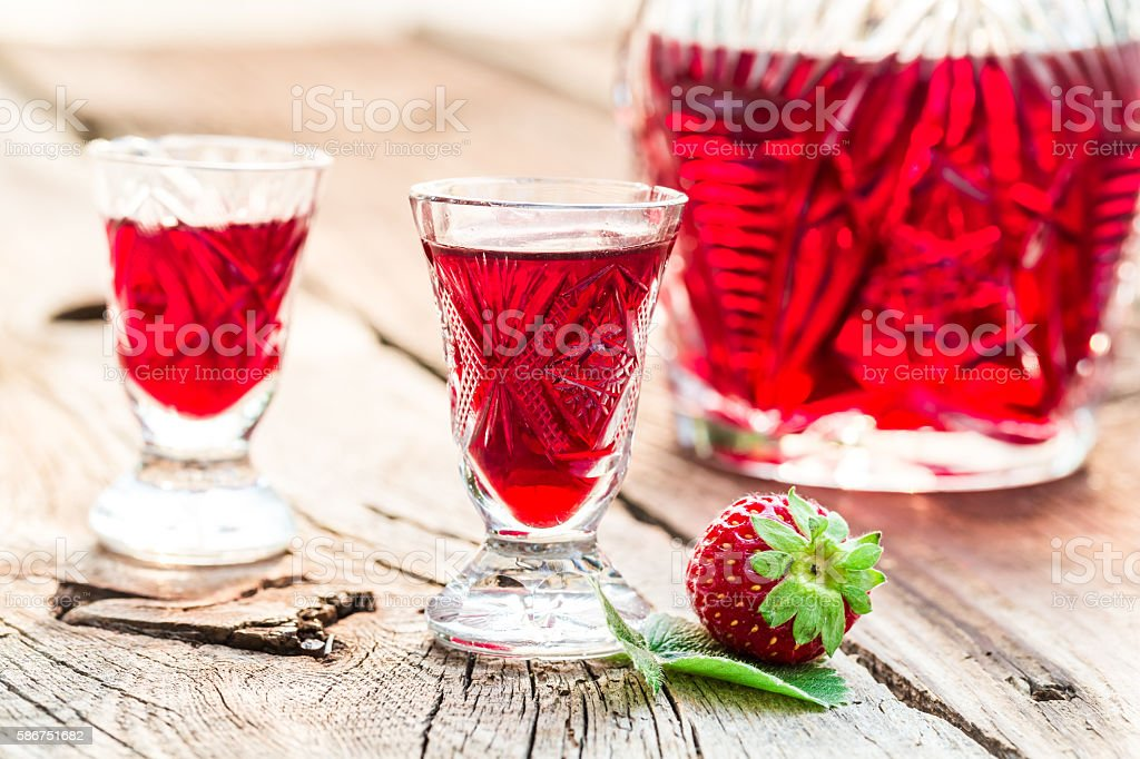 Homemade liqueur made of alcohol and strawberries stock photo