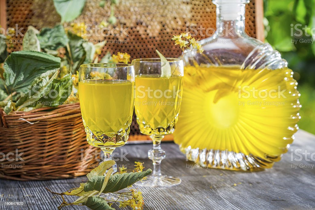 Homemade liqueur made of honey and lime in summer garden royalty-free stock photo