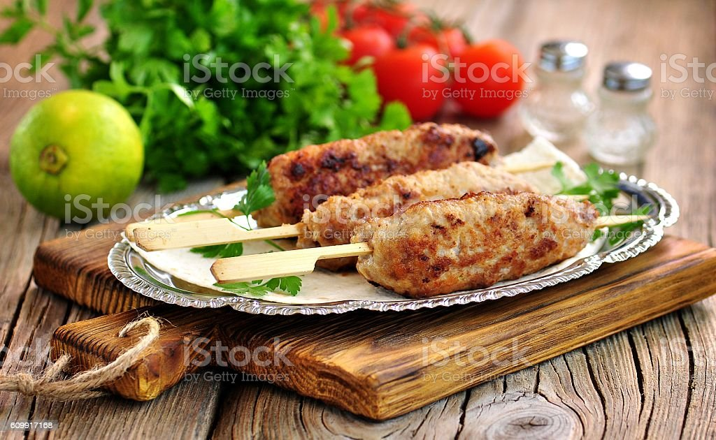 Homemade meat kebabs skewers with dogberry and onion salad stock photo