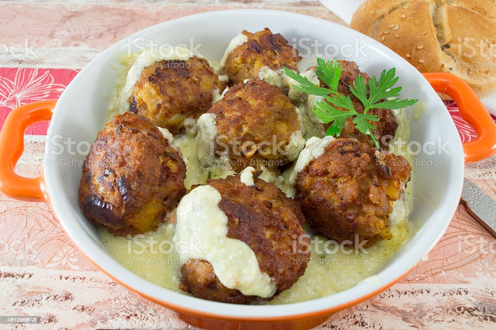 Homemade meatballs served in an orange bowl with corn bread stock photo