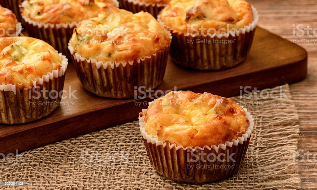 Homemade muffins with chicken and cheese on brown wooden board. stock photo