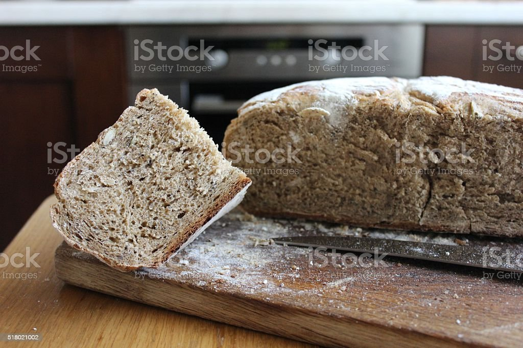 Homemade multigrain bread loaf and piece cut on wooden board stock photo