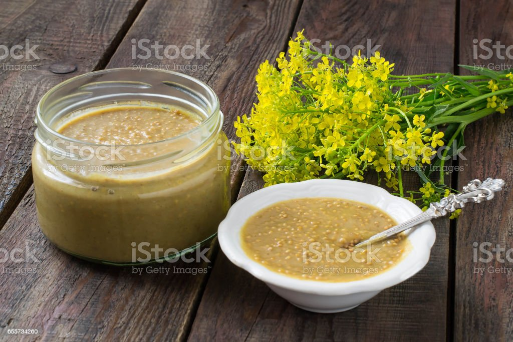Homemade mustard grains and mustard flowers stock photo