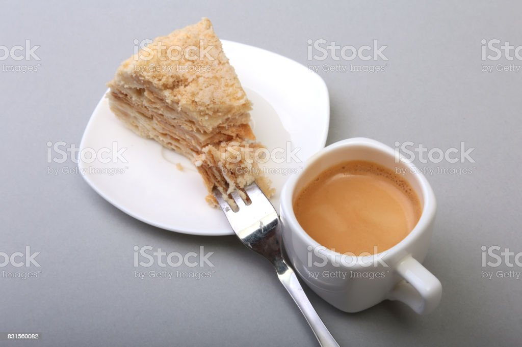 Homemade Napoleon puff cake on plate and traditional espresso coffee isolated on white background. close-up. stock photo
