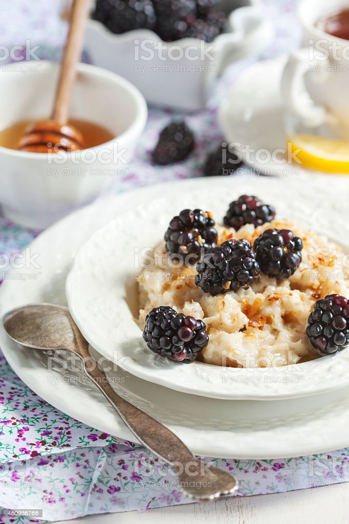 Homemade Oatmeal with Blackberries, granola and honey for Breakfast stock photo