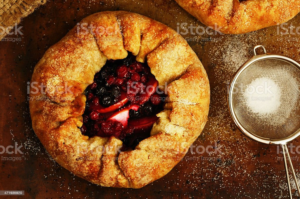 Homemade open pies or galette with apples and berry mix stock photo