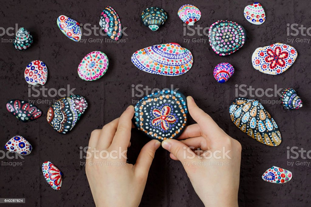 Homemade painted dot patterns on pebbles and shells. Step 5 stock photo