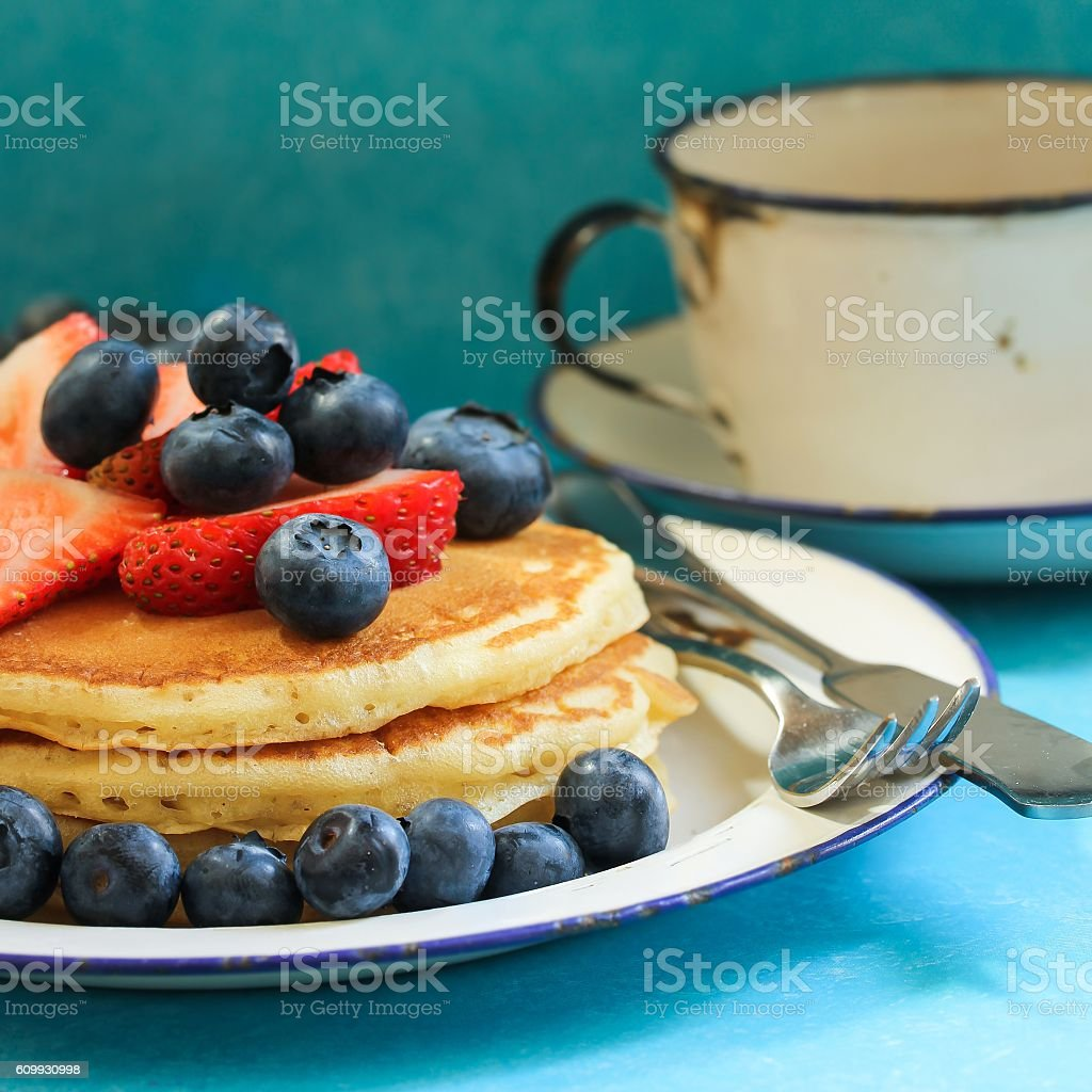 Homemade pancakes topped with fresh strawberries and blueberries, selective focus stock photo