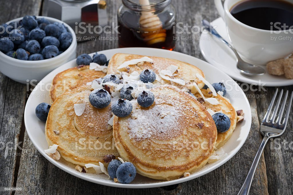 homemade pancakes with blueberries and powdered sugar stock photo