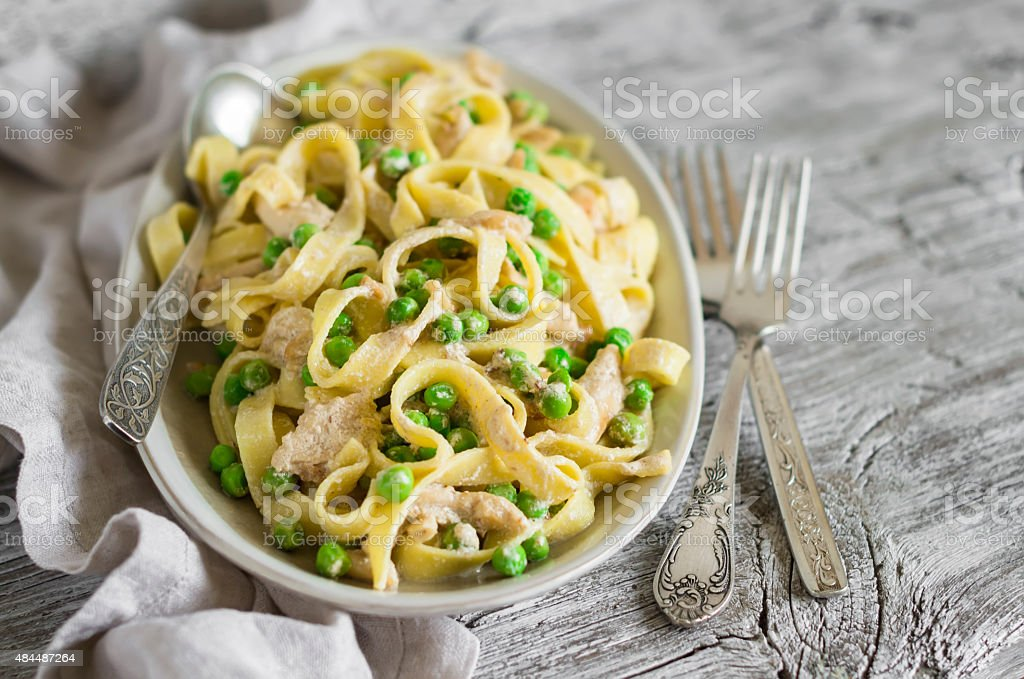 homemade pasta with chicken, green peas and cream sauce stock photo