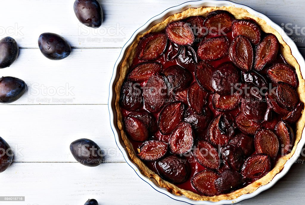 Homemade pie with plums on the table stock photo