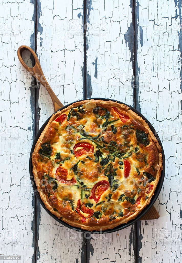 Homemade pie ( quiche) with spinach, tomatoes and soft cheese stock photo