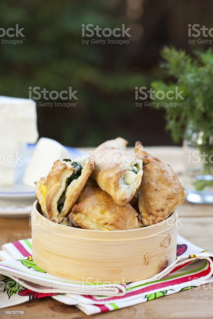 Homemade pies with spinach and cheese on wooden surface. royalty-free stock photo