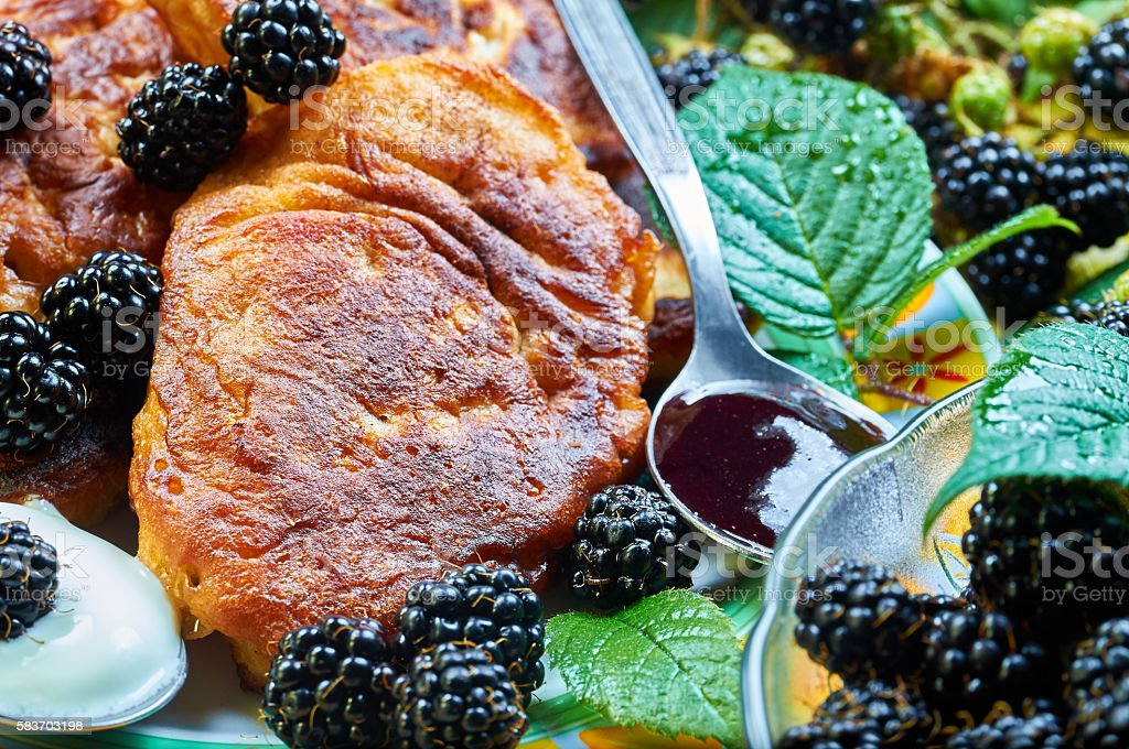 Homemade pikelets with forest blackberries and sweet cream stock photo