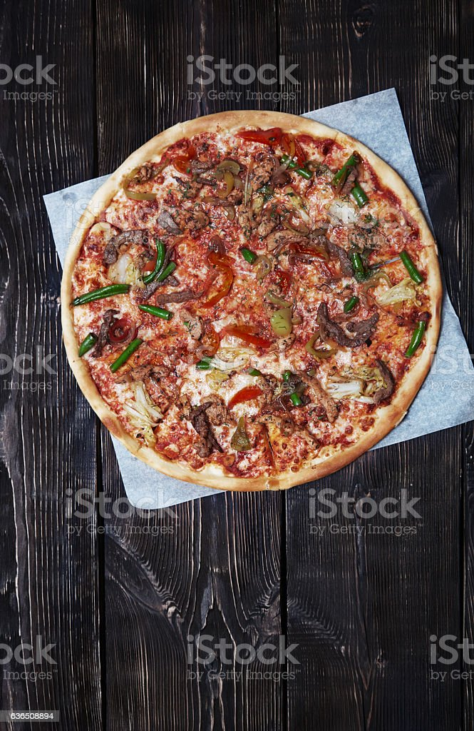 Homemade pizza on a wooden table stock photo