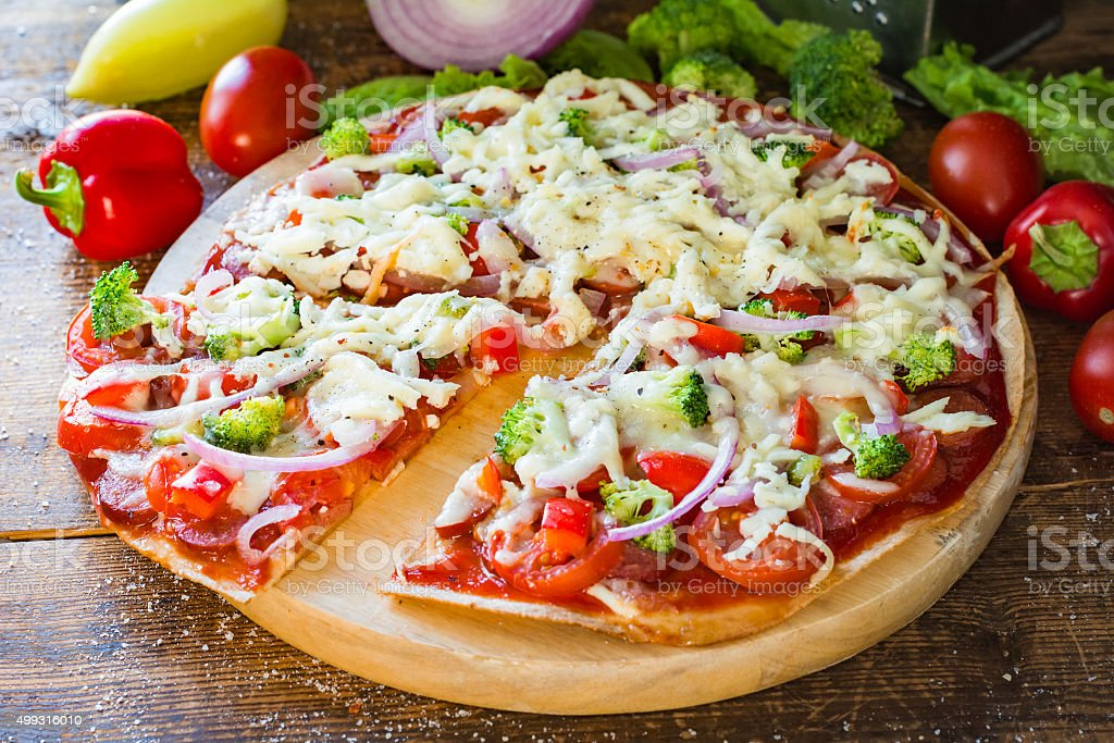 Homemade pizza on round cutting board stock photo